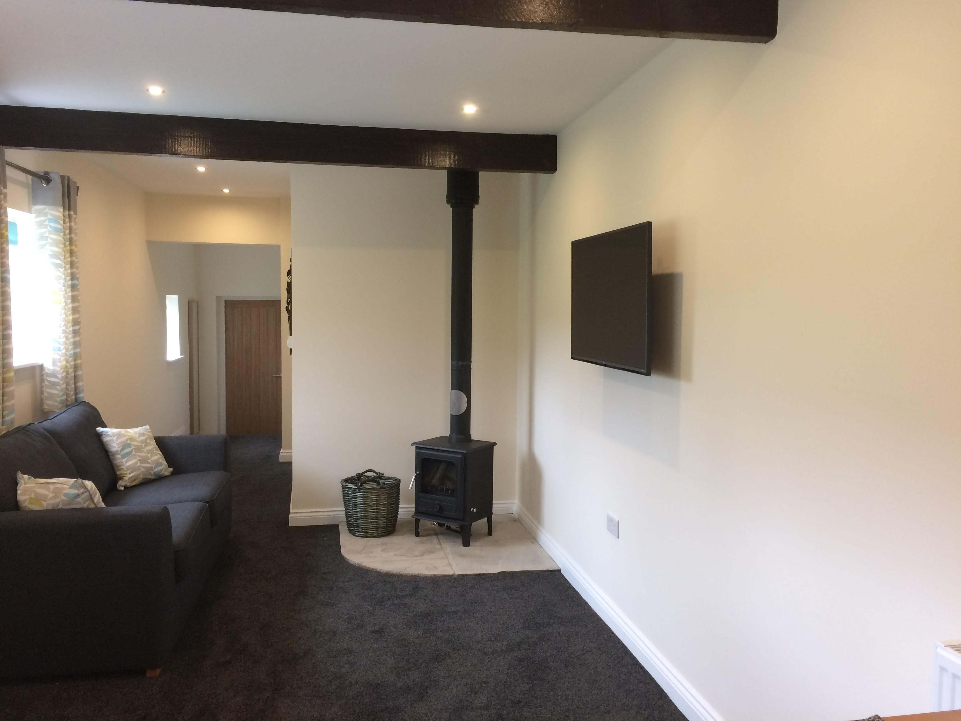 Living room area showing a comfy blue sofa, wood burning stove and HD Television